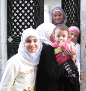 In the Aleppo souq, inside the ancient old walls of the city, four children enter an apartment with their mother.